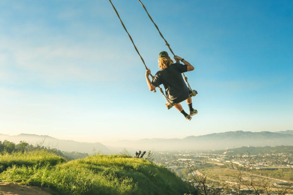 Man flies over landscape / cityscape on a swing.