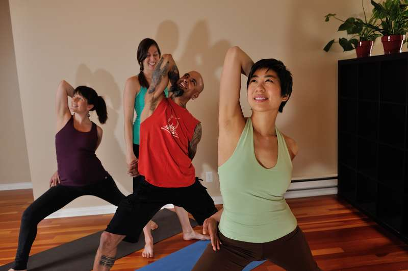 Three students in a standing posture with Gomukasana arms. One female student is white, a white male student has plenty of tattoos, another female student is of Asian descent.