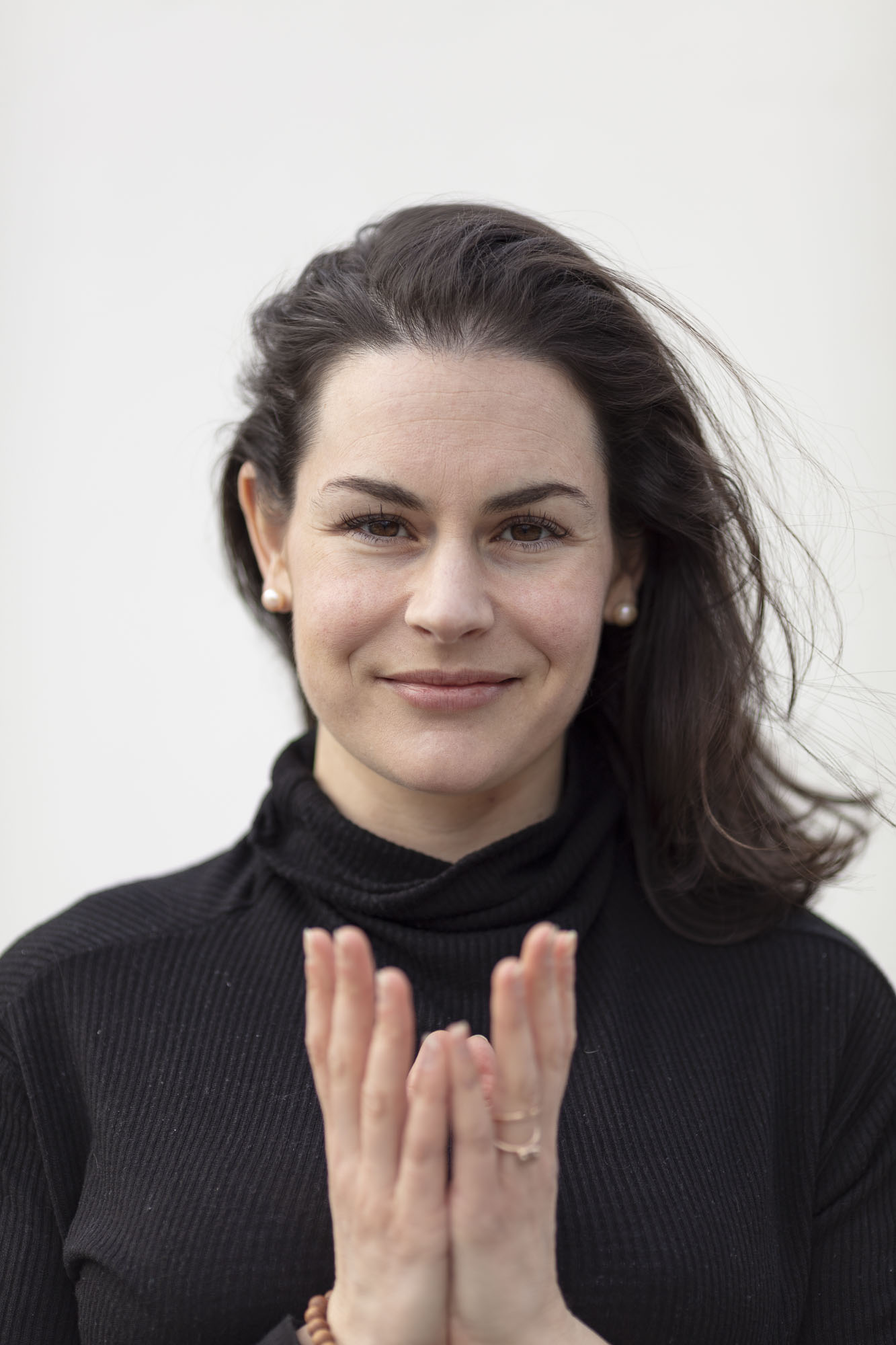a light skinned woman with dark hair that is wind blown holds cupped hands in front of her